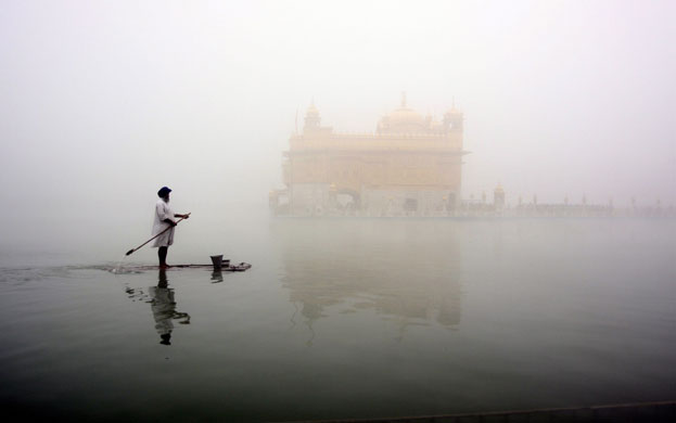 Amritsar-India-A-Sikh-man-on-a-makeshift-boat-cleans-the-holy-tank-of-the-Golden-Temple-–-Sikh-devotees-believe-a-bath-in-the-tank-will-cleanse-the-soul